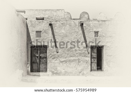 Sepia view of the inner courtyard of a traditional old Arabian adobe house in strong sunlight with shadows from wooden gutters and carved wooden doors and window lattices for ventilation. #575954989