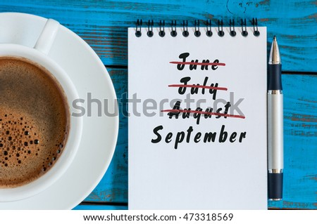 September beginning and summer end concept written at notepad with morning cup of coffee. Striked June, July, August