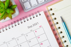 September 2021 calendar with note book on pink background.