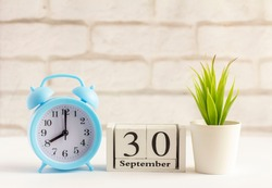 September 30 on a wooden calendar next to the alarm clock.September day, empty space for text.Calendar for September on a light background