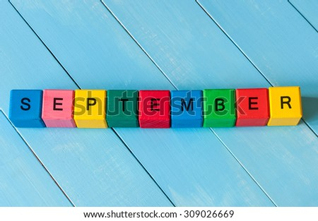 September sign on color wooden cubes with light blue wood background. Back to school time.