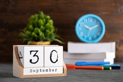 September 30th. September 30 wooden cube calendar with blur objects on background.