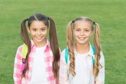 September. Vacation is over. Back to school. Cute schoolgirls with long ponytails. Ending of school year. Cheerful smart schoolgirls. Happy schoolgirls outdoors. Small schoolgirls with backpacks