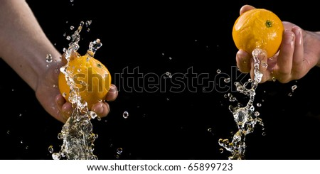 Sequence of oranges splashing in hand isolated black background