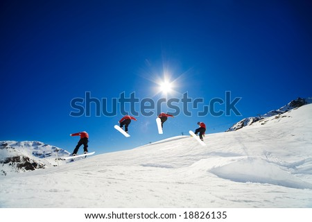 Sequence shot of snowboarder going over jump - stock photo