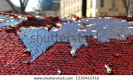 Sequin surface texture with blurred cityscape on background. Silver red two-sided sequins look like contours of continents. Shiny glitter background. Brilliant backdrop. Scales of round sequins #1330461416