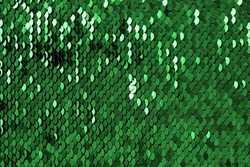 Sequins green shiny background.sequin pattern.Texture scales with Sequins.Scales background.Shiny texture material.iridescent fabric.sparkling sequined textile