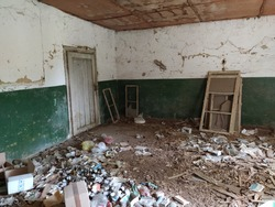 Serbia, Belgrade, May 10, 2020. Inside abandoned house. Grunge scene. Scattered trash on the floor. Green paint on the walls. White half wall. Shot wooden window frames. Bottles, pieces of paper