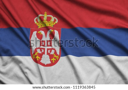 Serbia flag  is depicted on a sports cloth fabric with many folds. Sport team banner #1119363845