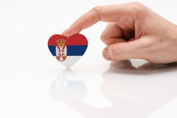 Serbia flag. Love and respect Serbia. A man's hand holds a heart in the shape of the Serbia flag on a white glass surface. The concept of Serbian patriotism and pride.