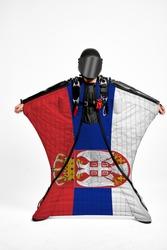 Serbia flag travel. Bird Men in wing suit flag. Sky diving men in parashute. Patriotism, men and flag.