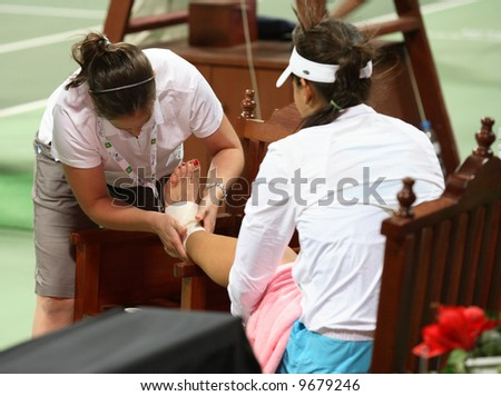Serbia\'s Ana Ivanovic has her ankle bandaged after falling on court in the final game of her Qatar Total Open debut against  Olga Govortsova, February 20, 2008.