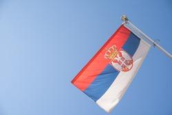 Serbian flag on a staff, isolated against blue sky