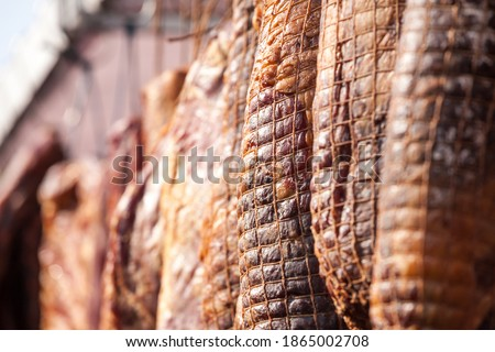 Serbian ham, called prsut, italian style, similar to prosciutto crudo, wrapped in a ham net hanging in the countryside of Serbia. Prosciutto is typical dry cured meat of pork produced in Italy, Spain Foto stock ©