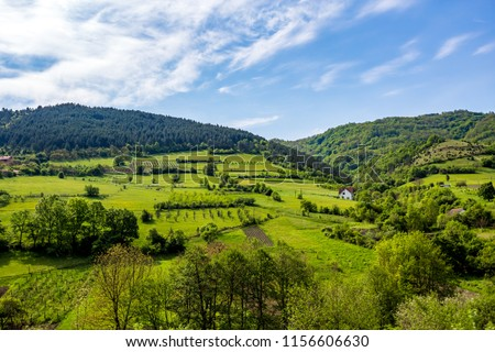 Serbian rural village green springtime landscape, mountains in Serbia are very beautiful, near Valjevo. Valley and hills. White house, farmland and spring forest in spring. European countryside #1156606630