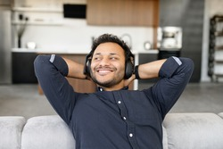 Serene and happy mixed-race guy wearing headphones listening music resting at home, smiling indian man enjoys favorite soundtracks sitting on the couch in cozy living room, looks away dreamly