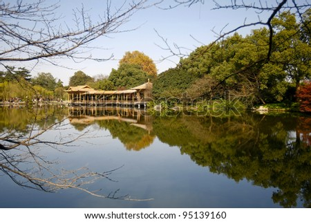 Serene and tranquil lake, reflecting a building at the West Lake in Hangzhou, China.