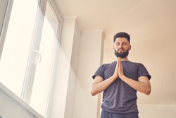 Serene bearded man closing eyes and doing prayer pose with hands in yoga studio