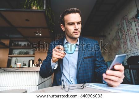 Serene businessman looking at mobile