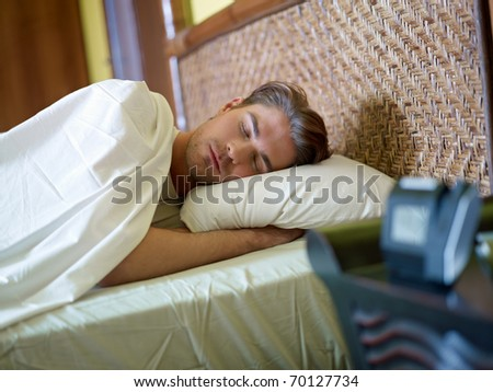 serene caucasian adult man lying in bed with alarm clock in foreground. Horizontal shape, waist up, front view