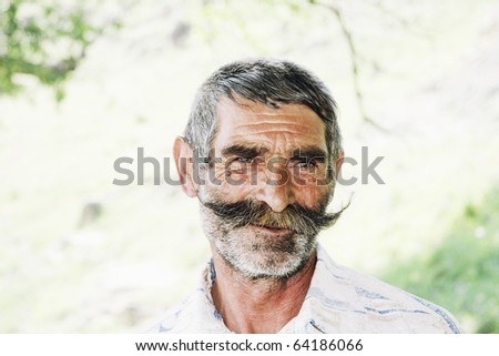 Serene elderly man with great mustaches closeup outdoors photo