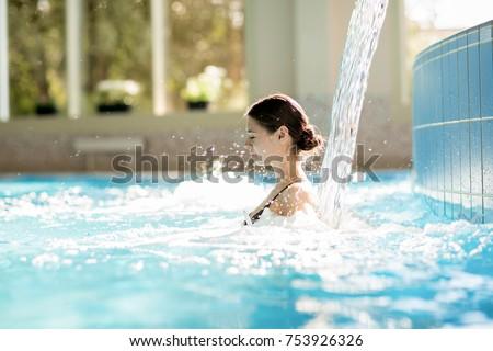Serene girl enjoying stream of waterfall and its gentle splashes in swimming-pool at spa resort #753926326