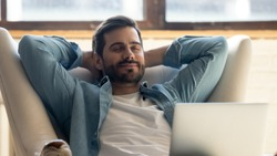 Serene happy healthy young man relaxing on comfortable armchair with laptop, smiling calm relaxed guy lounge eyes closed in sunny cozy home with notebook device enjoying lazy leisure lifestyle on