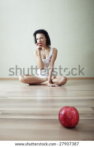 Serene lady at home sitting on the floor and eating apple