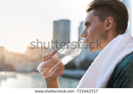 Serene male athlete drinking bottle of water