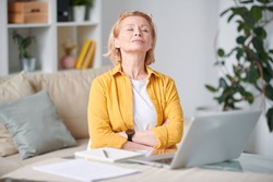 Serene mature blond woman in casualwear relaxing on couch in front of laptop with her eyes closed during remote work at home