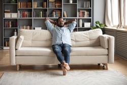 Serene relaxed barefoot young african man resting on comfortable couch in modern living room holding hands behind head, millennial hipster guy enjoy no stress peace of mind lounge on sofa at home