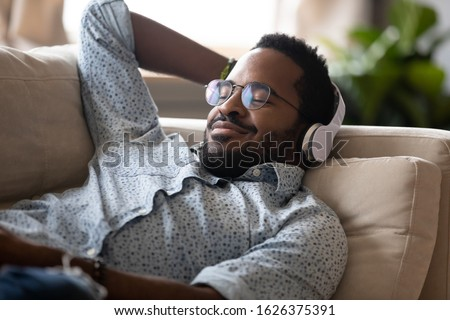 Serene satisfied young adult african american man lying on comfortable sofa wear wireless headphones enjoy listen modern music audio book with eyes closed meditate relax feel no stress chill at home