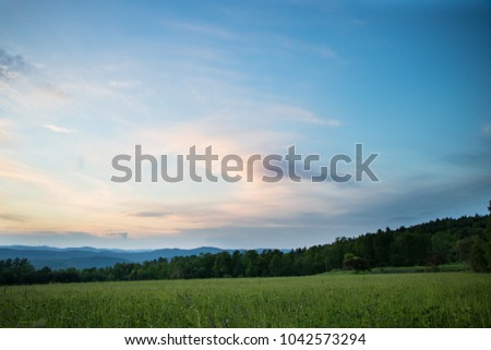 Serene sunset over a field with a mountain view  #1042573294