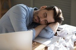 Serene unproductive office employee put head on arms sleeping at desk with laptop, document, crumpled papers. Hard workday, monotonous boring paperwork, stress, chronic fatigue, sleep disorder concept