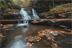 Serene waterfall surrounded by Autumn colors in October 2020 at Ricket's Glen State Forest.