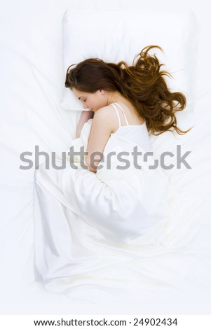 Serene woman covered with silk cloth lying in bed and having a nap