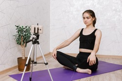 Serene woman in Easy Sit pose sitting on mat and watching online video tutorial on smartphone on tripod while doing yoga at home and stretching athletic body