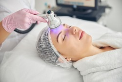 Serene young Caucasian female patient with closed eyes being treated by a purple light wavelength