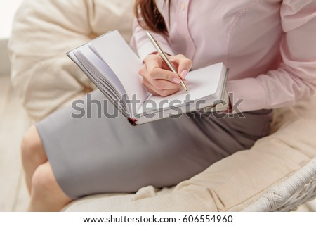 Serene young female inscribing in notebook #606554960