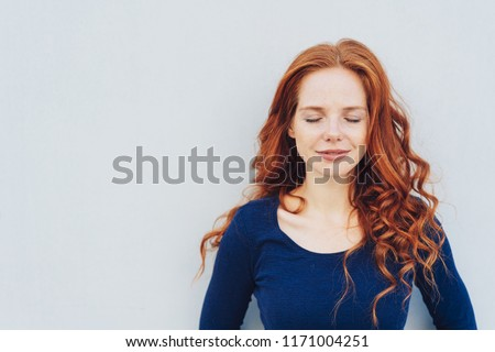Serene young redhead woman taking a moment to relax or meditate standing with closed eyes against a white wall with copy space #1171004251