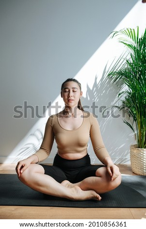 Serene young woman practicing yoga, meditating with her eyes closed in a big studio. Frontal view. She's sitting in easy pose, her eyes closed. She's wearing tight top and shorts Stock fotó ©