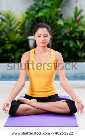 Serene young woman sitting in lotus position while practicing Hindu yoga outdoors