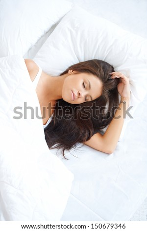 Serene young woman sleeping peacefully in bed dreaming sweet dreams  high angle portrait