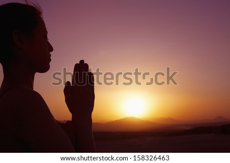Serene young woman with hands together in prayer pose