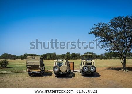 SERENGETI, TANZANIA - AUGUST 27, 2015: Safari cars waiting to clients in the Kogatende airstrip in northern Serengeti, Tanzania, Africa