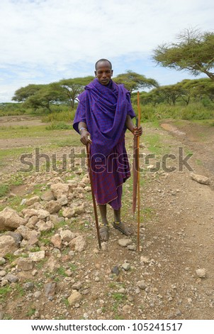SERENGETI, TANZANIA - JAN 22: An unidentified African man in traditional dress from Masai tribe shown in the savannah in the Serengeti National park on January 22, 2008.