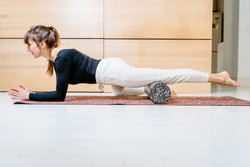 Seria photo of woman using foam roller for exercise at home. Method to release tension and help with muscle pain, a tool for exercise, physical therapy and training. Pilates,healthy lifestyle theme