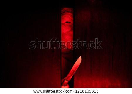 Serial killer / eye peeking behind the door with kinfe