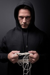 Serial killer with rope in hands, looking at camera, commit crime, isolated on black studio. aggression, crime concept. Portrait of caucasian male pedophile maniac, copy space. kidnapping, violence