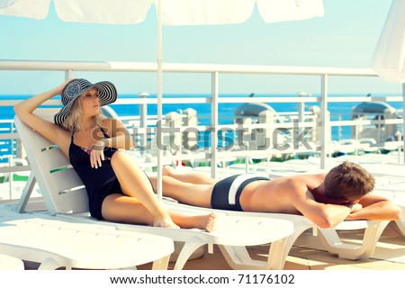 Series man and woman lying on chaise lounges on a yacht in the ocean